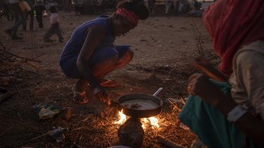 Tigray women who fled the conflict in Ethiopia's north, cook at a refugee camp in eastern Sudan on Friday.