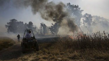 An Israeli firefighter battles a fire started by an incendiary device launched from the Gaza Strip.