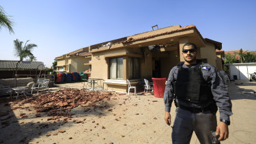 A policeman stands in front of a house hit by a rocket fired from Gaza Strip in Netivot, Israel.