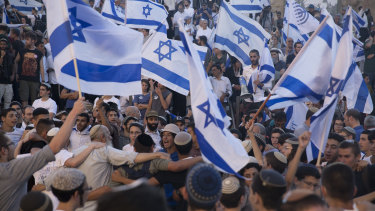 Ultra-nationalist Israelis dance with Israeli flags as they march near Damascus Gate.