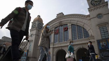 Travellers walk past Hankou railway station on the eve of it resuming outbound traffic in Wuhan.