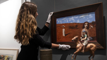 "Madeleine Norton straightens the Gary Shead painting ""Bettany's Book"" at the Leonard Joel auction house in Sydney."
