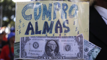 "Fake US dollar bills stapled to a sign with the message: ""I buy souls"" at a pro-government demonstration."