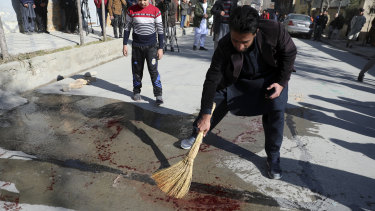 An Afghan man sweeps blood off a Kabul street after a Taliban attack on two female judges in January.
