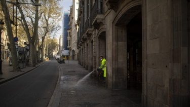 A worker disinfects the street to prevent the spread of COVID-19 in Barcelona, Spain, Thursday, March 19, 2020.