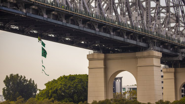 A climate activist dangles from the Story Bridge during week-long protests by Extinction Rebellion.