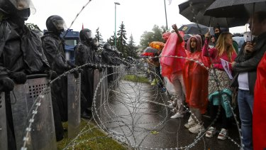 Protesters argue with police standing in front of a police barricade blocking opposition rally from moving toward the Independence Palace, residence of the President Alexander Lukashenko in Minsk.