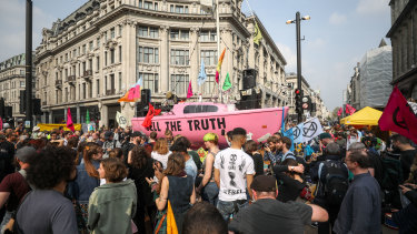 Climate activists surround a pink boat during a protest near Oxford Circus London Underground station.