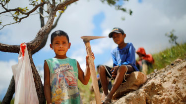 Indigenous children pose at a gold mine at the Santa Creuza community in indigenous land, Roraima state, Brazil.