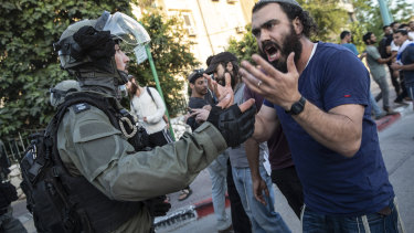 Israeli riot police try to block a Jewish right-wing man as clashes erupted between Arabs, police and Jews, in the mixed town of Lod,  Israel.