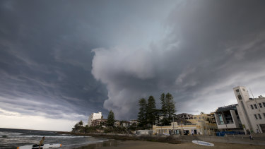 A storm rolls into Cronulla beach, where Reserve Bank research shows climate change could increase the cost of property insurance.