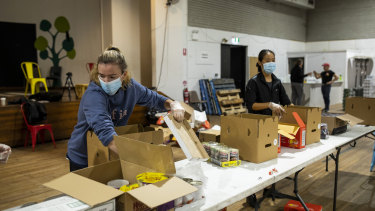Waverley Old Boys Football Club player Anna Morrison helps pack boxes of essential goods for people in need with the Addi Road Food Pantry.