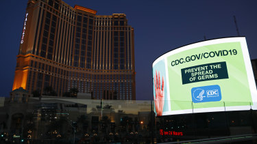 A sign advises people to minimized the spread of germs, along the Las Vegas Strip devoid of the usual crowds during the coronavirus outbreak Tuesday, May 26, 2020, in Las Vegas.