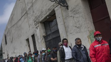 People wearing masks to curb the spread of the new coronavirus wait for food outside the San Francisco de Asis soup kitchen which is handing out food for the homeless and poor in Lima, Peru.