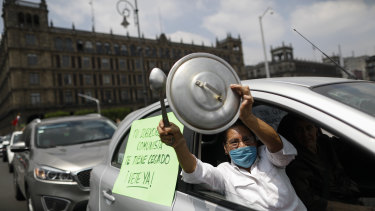 """A woman bangs a pot lid next to a sign reading in Spanish; """"Your communist ideology is blinding you, leave already!"""" during a protest calling for Mexican President Andres Manuel Lopez Obrador to step down."""