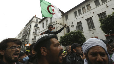 A man holds an Algerian flag while Algerians demonstrate to mark the second anniversary of the Hirak movement.