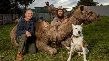 Expeditioner John Elliott (right) with his camel train and dog Bruski in Lakes Entrance catches up with camel trainer Russell Osborne.