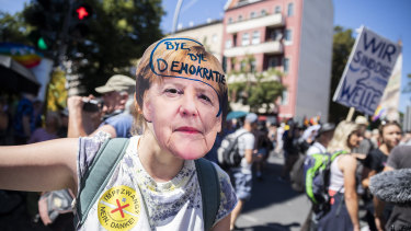 """A woman wears a Angela Merkel mask with the inscription """"Bye bye democracy"""" at a demonstration against the Coronavirus restrictions in Berlin."""
