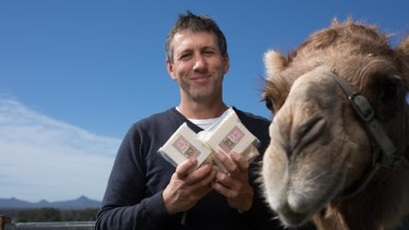Summer Land Camels' Jeffrey Flood with one of farm's resident camels and some of the signature camel cheddar.