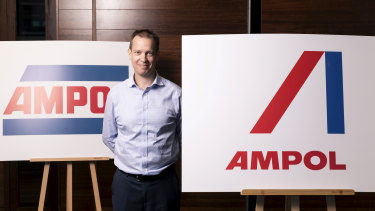 Caltex interim chief executive Matthew Halliday with the old Ampol logo (left) and the new logo (right).