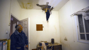 An Israeli man looks at rocket damage in a house in Sderot, southern Israel, on Monday.