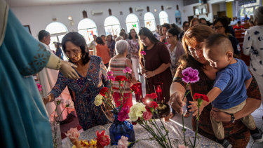 Jeanie Bamba holds her grandson, Jayce, as they lay flowers at Immaculate Heart of Mary Catholic Church in Toto, Guam, on Mother's Day. Catholicism is deeply engrained in Chamorro culture.
