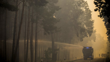 A police water cannon sprays water into a forest near Treuenbrietzen, south of Berlin.