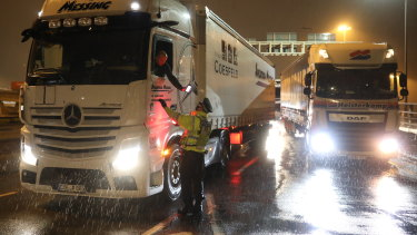 A police officer checks a truck driver's information as it rains in Dover.