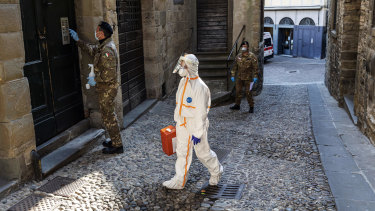 A Red Cross worker visits to the home of a COVID-19 patient in Bergamo, Italy.