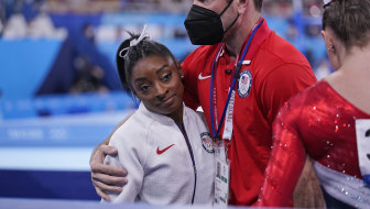 Coach Laurent Landi embraces Simone Biles after she quit the Team final at the Olympics.