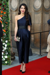 Amal Clooney in a black tie jumpsuit, one of 2010s key fashion trends.