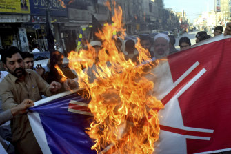 Pakistan traders burn a representation of the French flag during a protest on Monday.