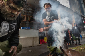 Raymond Noel's father, Raymond Thomas, takes part in a smoking ceremony outside the Coroners Court on Friday.