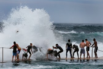 A regular scene at Bronte beach: teenagers cling onto the railing as large waves break over the top of them.
