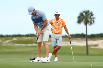 Rickie Fowler watches Rory McIlroy putt during their fundraising match.