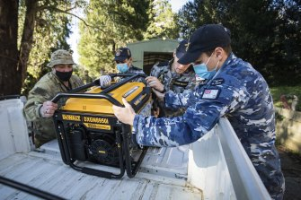 Members of the ADF prepare to load generators to distribute to residents in the storm-ravaged Dandenong Ranges last Sunday.