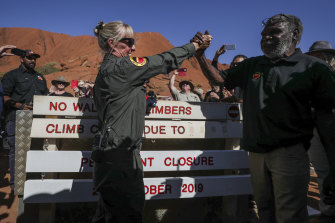 Ranger Lynda Wright celebrates with Chair of Uluru-Kata Tjuta national park, Sydney James, after placing the new sign of the permanent closure of the Uluru climb