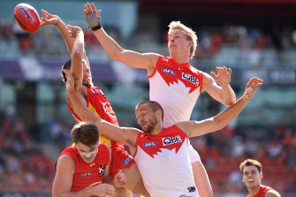 Isaac Heeney attacks the pack against Gold Coast with his recently-broken right hand covered by a protective glove.