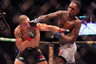 Robert Whittaker (left) is hit by Israel Adesanya (right) as they compete during UFC 243.