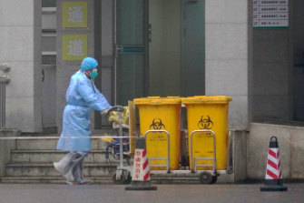 A staff member moves bio-waste containers past the entrance of the Wuhan Medical Treatment Centre in January 2020, the early days of the pandemic.