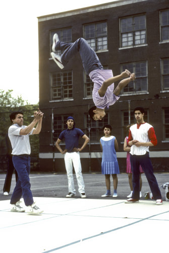 """Members of the Rock Steady Crew, including the group's co-founder Richard """"Crazy Legs"""" Colon (red sleeves, rear right),  breakdance at Booker T. Washington Junior High School in New York in 1983."""