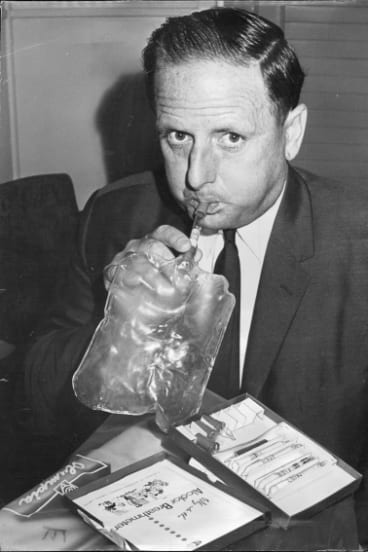 The NSW Transport Minister, Mr. Milton Morris, who is teetotaller, demonstrates the use of a breath tester on March 10, 1968.