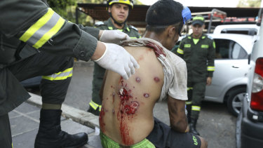 A youth's back is inspected by a medic after he was injured during clashes with Venezuelan National Guardsmen on the Simon Bolivar International Bridge in La Parada, Colombia, on Monday.