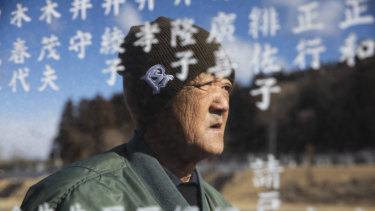 Noboru Honda, a local community leader, stands near the monument inscribed with the names of the victims of the 2011 earthquake and tsunami in Namie, Japan.