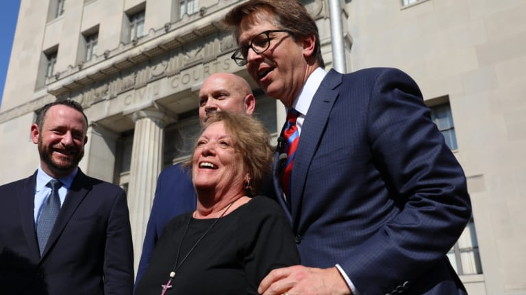 Plaintiff Gail Ingham  stands outside the civil courthouse with attorneys Lee Cirsch, from left, Eric Holland and Mark Lanier following the verdict.