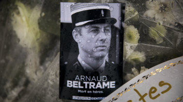 A photo of Lieutenant Colonel Arnaud Beltrame placed on a bunch of flowers at the main gate of the Police headquarters in Carcassonne.