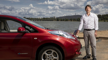 Denby Angus with his electric car, the Nissan Leaf, which was imported from overseas.