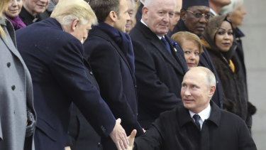 Russian President Vladimir Putin shakes hands with US President Donald Trump.