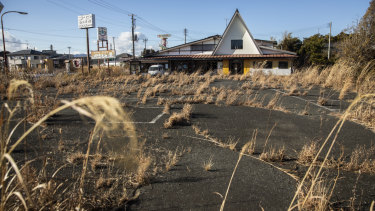 Weeds grow in the parking lot of an abandoned restaurant along Route 6, just outside the exclusion zone around the Fukushima plant.