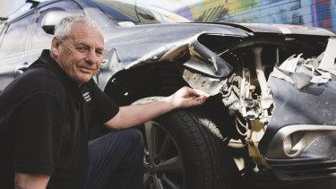 Owner of Braddon Smash Repairs, Jeff Badcoe with a car that has damage from hitting a kangaroo.